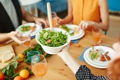 Amis passant la salade à la table tout en mangeant ensemble Images libres de droits