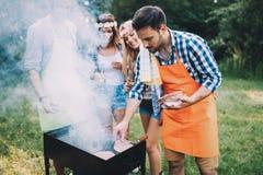 Amis passant le temps en nature et ayant le barbecue Photos libres de droits