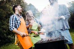 Amis passant le temps en nature et ayant le barbecue Photos stock