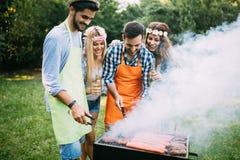 Amis passant le temps en nature et ayant le barbecue Photographie stock libre de droits