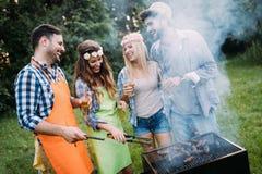 Amis passant le temps en nature et ayant le barbecue Photographie stock