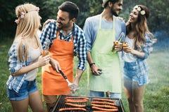 Amis passant le temps en nature et ayant le barbecue Images stock