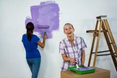 Amis peignant un mur Images libres de droits