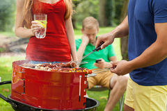 Amis pendant griller sur un barbecue Photo libre de droits