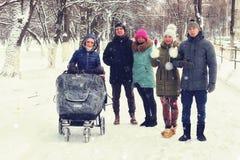 Amis pendant l'hiver avec une poussette Photo stock