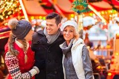Amis pendant la saison du marché ou d'avènement de Noël Photos libres de droits