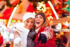 Amis pendant la saison du marché ou d'avènement de Noël Photo libre de droits