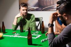 Amis pendant un jeu de dominos la nuit Image libre de droits