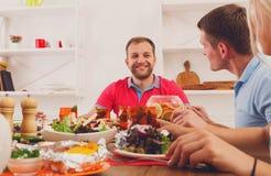 Amis, personnes heureuses à la table servie pour le dîner Images libres de droits