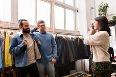 Amis photographiant au magasin d'habillement de vintage Photographie stock libre de droits