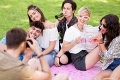 Amis photographiant au pique-nique en parc d'été Photographie stock