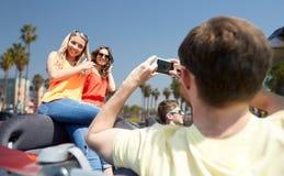 Amis photographiant dans la voiture au-dessus de la plage de Venise Photo libre de droits