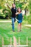 Amis plaing les jeux de plein air - lancer d'anneau Le type et la fille concurrencent dans le lancer d'anneau image stock