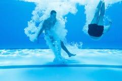 Amis plongeant dans la piscine Image libre de droits