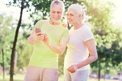 Amis pluss âgé intéressés à l'aide du téléphone portable Images libres de droits