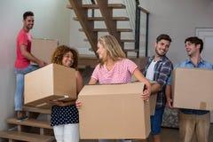 Amis portant des boîtes en carton dans la nouvelle maison Images stock