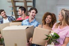 Amis portant des boîtes tout en replaçant dans la nouvelle maison Images libres de droits