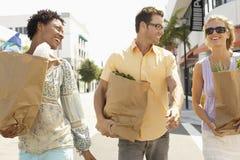 Amis portant des sacs d'épicerie sur la rue Photographie stock