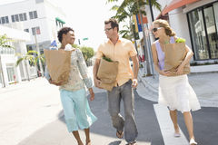 Amis portant des sacs d'épicerie sur la rue Photo stock