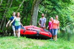 Amis portant le canot en caoutchouc à la rivière de forêt Images libres de droits