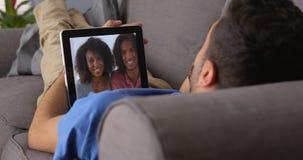 Amis portoricains heureux parlant sur le comprimé Images stock
