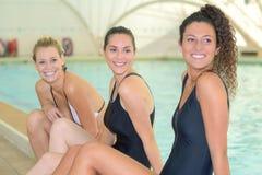 Amis posant à la piscine Photos stock