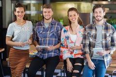 Amis posant avec des téléphones portables et des comprimés numériques dans le restaurant Images stock