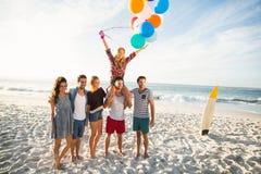 Amis posant avec le ballon sur le sable Images stock