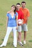 Amis posant avec un football Images stock