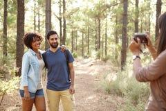 Amis posant pour des photos dans une forêt Image stock
