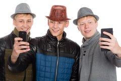 Amis posant pour un individu dans le chapeau Photographie stock