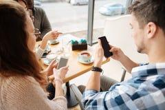 Amis positifs à l'aide des smartphones en café de tha Image stock