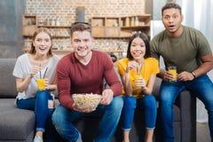 Amis positifs émotifs se sentant heureux tout en observant un film Image stock