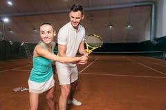 Amis positifs apprenant à jouer au tennis Photos libres de droits
