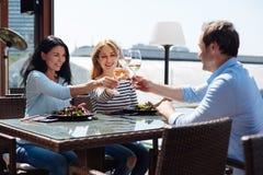 Amis positifs avec plaisir se réunissant au restaurant Images stock