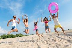 Amis positifs ayant l'amusement sur la plage Images libres de droits