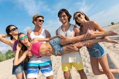 Amis positifs ayant l'amusement sur la plage Photo libre de droits