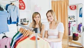 Amis positifs choisissant des vêtements dans la mémoire de vêtements Photos stock