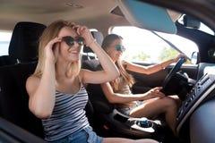 Amis positifs conduisant une voiture Images libres de droits
