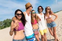 Amis positifs embrassant sur la plage Image libre de droits