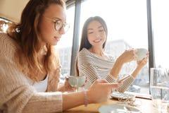 Amis positifs modernes s'asseyant dans le café Photo stock