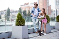 Amis positifs montant le scooter de coup-de-pied Image libre de droits