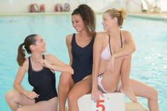 Amis positifs nageant dans la piscine Photos libres de droits