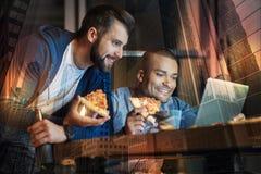 Amis positifs observant des films tout en mangeant de la pizza ensemble Photos stock