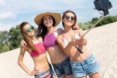 Amis positifs prenant des photos sur la plage Photographie stock libre de droits