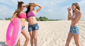 Amis positifs prenant des photos sur la plage Photo libre de droits