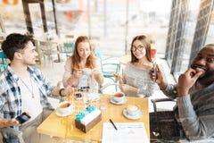 Amis positifs s'asseyant à la table Photographie stock libre de droits