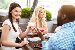 Amis positifs s'asseyant dans le café Photographie stock libre de droits