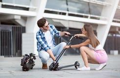 Amis positifs tenant le scooter de coup-de-pied Photographie stock