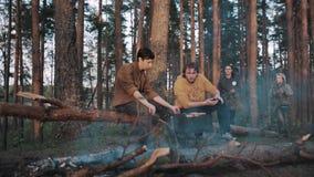 Amis pour deux hommes s'asseyant sur des bois d'identifiez-vous, faisant cuire le barbecue et parler clips vidéos